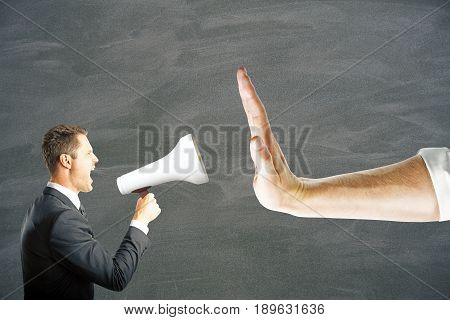 Hand gestures no to businessman screaming into megaphone on chalkboard background. Lack of communication concept