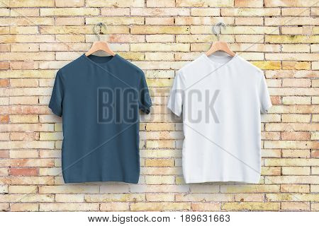 Hangers with empty grey and white t-shirts hanging on brick wall. Apparel concept