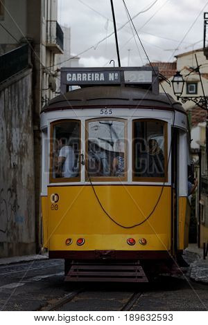 LISBON, PORTUGAL - MAY 9, 2017: People in the vintage tram near Saint Vincent church. First electric tramway in the city commenced operations in 1901, and now the system comprises five urban lines
