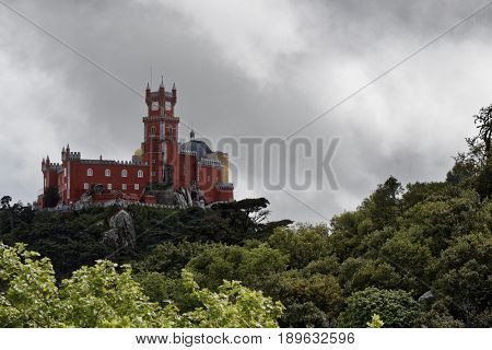 SINTRA, PORTUGAL - MAY 10, 2017: View to Pena Palace located on the top of hill in Sintra mountains. Since 1995, the cultural landscape of Sintra is listed as UNESCO World Heritage