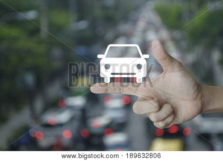 Car flat icon on finger over blur of rush hour with cars and road Business service car concept