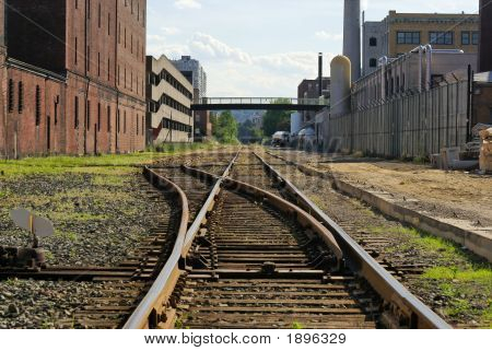 railroad track switching station converging in the distance in cambridge massachusetts flanked by factory buildings poster