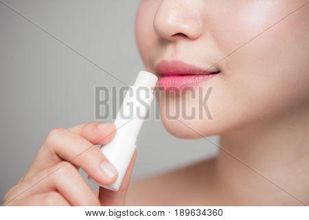 Asian Woman Applying Hygienic Lip Balm Over Grey Background