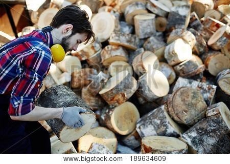 Young worker carrying log while working at lumberyard