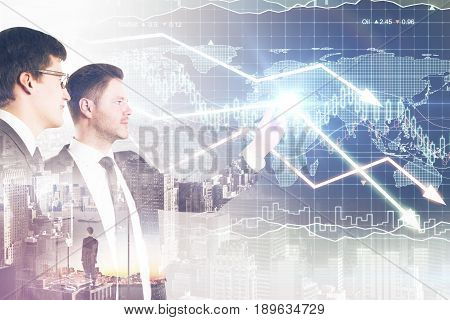 Two attractive businessmen drawing downward forex chart arrows on city background. Profit concept. Double exposure