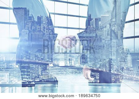 Side view of businesspeople shaking hands on abstract city background. Partnership concept. Double exposure