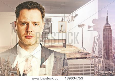 Portrait of attractive young businessman on abstract city and studio background. Cinematography concept. Double exposure