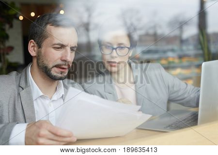 Confident professionals reading papers and discussing them