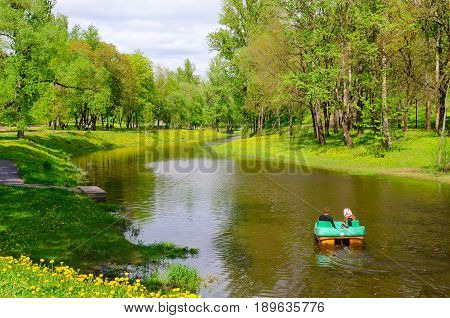 VITEBSK BELARUS - MAY 21 2017: Unknown people ride on catamaran on River Vitba in park of culture and rest named after Frunze on sunny day in May Vitebsk Belarus