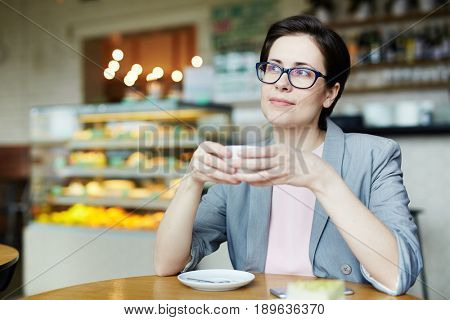 Young woman with cup of tea sitting in cafeteria