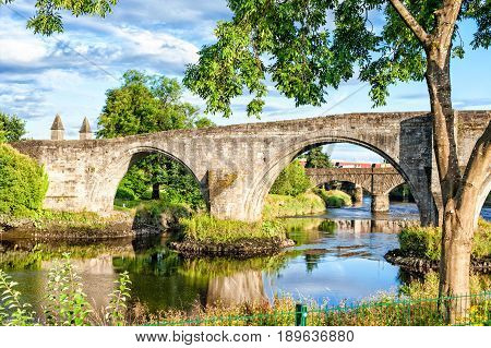 The old stone bridge of Stirling on the cloudy blue sky background. Summertime outdoors in Scotland..