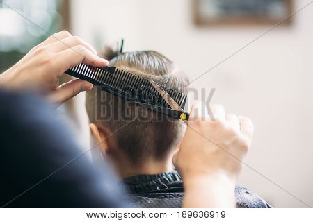 Little Boy Getting Haircut By Barber While Sitting In Chair At Barbershop.