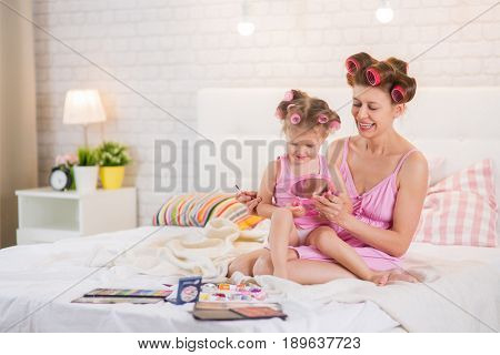 Mom and daughter in the bedroom on the bed in the curlers make up, paint their nails and have fun