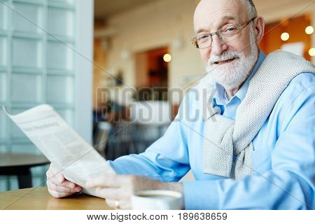 Mature man with newspaper looking at camera