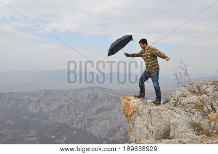 Young man with umbrella on a cliff edge on the top of mountain. Dangerous cliff on top of the mountain