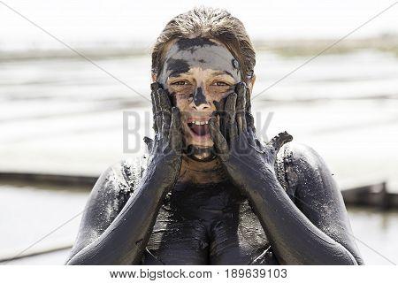 Woman Giving Himself A Mud Bath