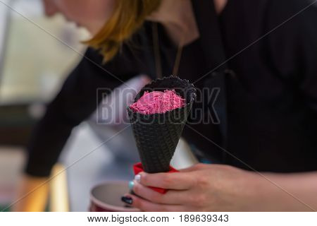 Young saleswoman in an ice cream parlor putting Bright pink fruit ice cream balls in Black waffle cone. Selective focus, for background