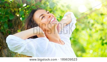Beautiful Young Woman Enjoying nature Outdoor. Happy and Healthy Smiling brunette Girl with healthy smile relaxing in the Summer Park. Breathing fresh air. Sunny day. Health care concept