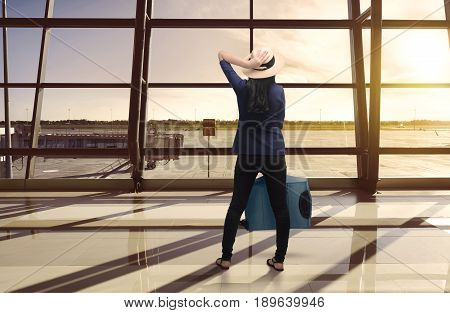 Portrait Of Asian Woman Carrying Luggage While Standing