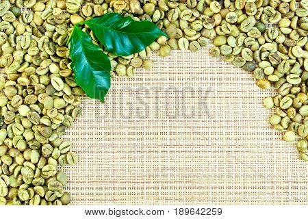 Frame of green coffee beans with leaves on a yellow coarse woven fabric