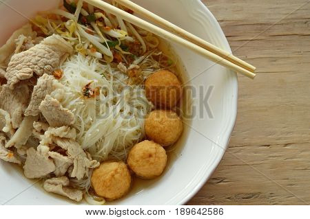 rice vermicelli topping shrimp ball and slice boiled pork in soup eat by wooden chopstick
