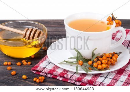 Tea of sea-buckthorn berries with honey on wooden table isolated on white background.