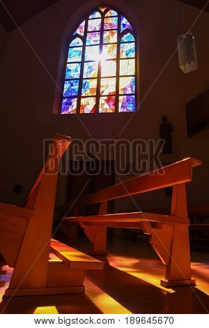 Modern Stained Glass Windows Reflecting Colors On Church Pews