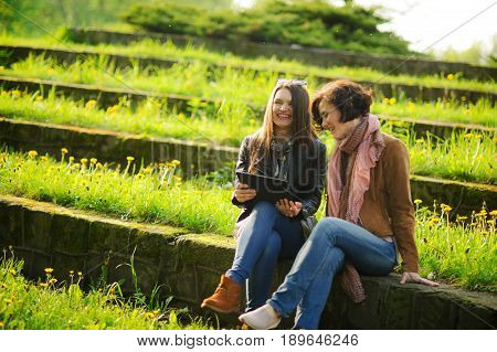 Two young charming women sit at stone steps with the tablet in hands. Girlfriends with interest look at the screen. Pleasant outdoor recreation in spring day. Young green grass and yellow dandelions.