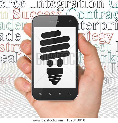 Finance concept: Hand Holding Smartphone with  black Energy Saving Lamp icon on display,  Tag Cloud background, 3D rendering