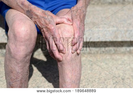 Old Man With Gnarled Hands Clutching His Knee
