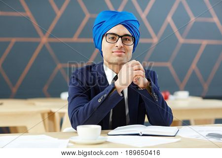 Young businessman in blue turban and suit sitting by workplace