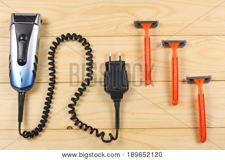 Electric shaver with razors on wooden table top view