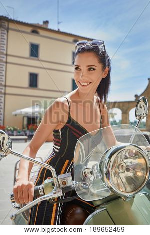 Young beautiful italian woman sitting on a vintage scooter.