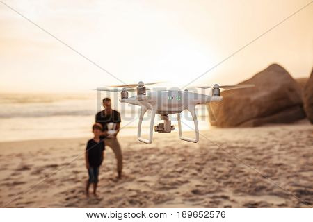 Drone Being Operated By Father And Son On Beach