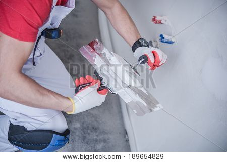 Drywall Patching Job. Apartment Remodeling. Caucasian Construction Worker with Patching Material and Tools.