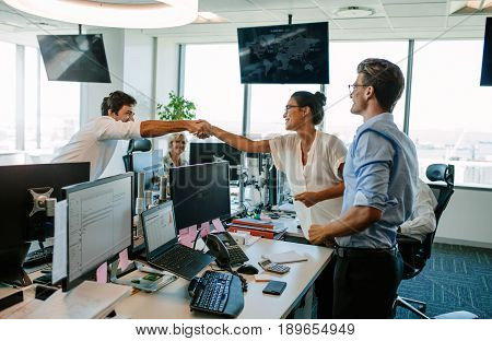 Business colleagues shaking hands in office. Happy business people celebrating success in modern office.