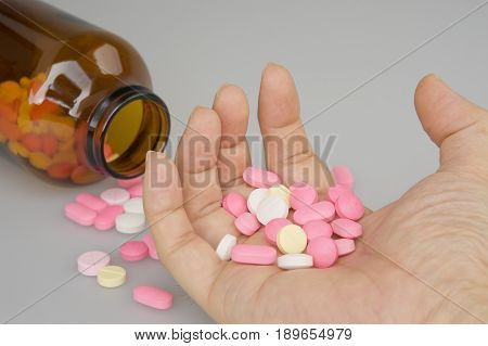 Contraction Hand Holding Colorful Tablets Have Blur Brown Bottle