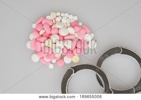 Handcuffs And Stack Of Tablets Place On White Background