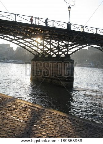 PARIS FRANCE - JANUARY 3 2010: Paris bridge crossing the river Seine in morning sunlight from the right bank on January 3 2010 in Paris France.