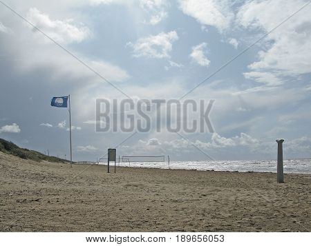 Sandy blue flag beach at Skrea Strand on a windy and sunny day with dark clouds in Falkenberg Sweden.