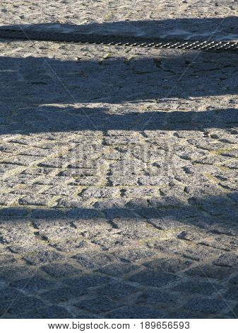 Cobble stone vertical background with shadows in winter light in Paris France.