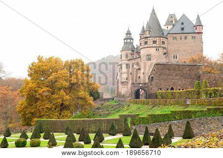 Burresheim Castle with triangle shaped topiary green trees in old ornamental garden in autumn Germany. Schloss Bürresheim Mayen. Outdoors horizontal image