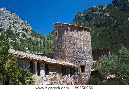 MALLORCA SPAIN - MAY 15 2017: Rustic stone building with tower in green subtropical garden in the Tramuntana mountains on May 15 2017 in Mallorca Spain.
