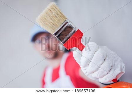 Paintbrush Painting Job. Caucasian Room Painter Showing His Brand New Paintbrush.