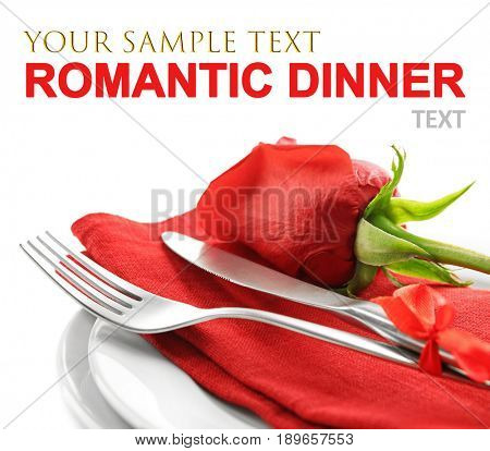 Text ROMANTIC DINNER and elegant table setting with rose on white background, closeup