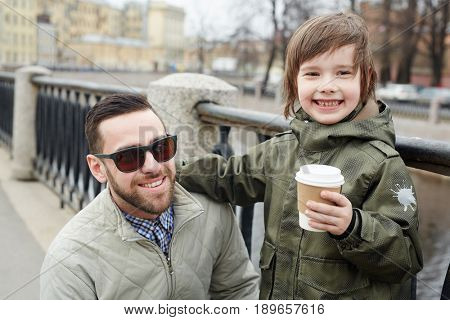 Smiley man and his son with drink spending leisure outdoors