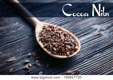 Aromatic cocoa nibs with spoon and text on wooden background