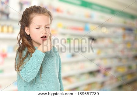 Allergies or cold concept. Little girl coughing at pharmacy