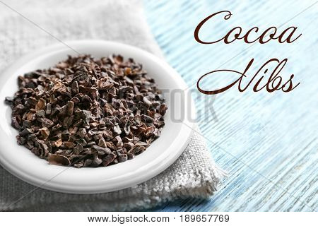 Saucer of aromatic cocoa nibs with napkin and text on wooden background