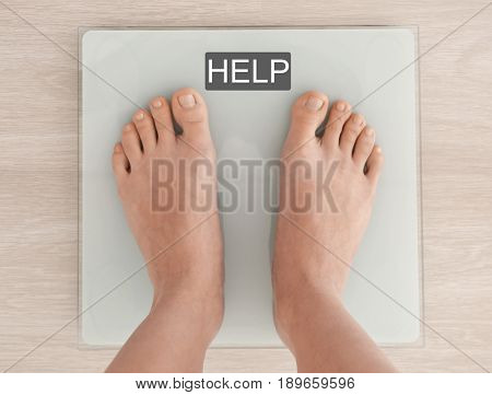 Weight loss concept. Woman standing on scales. Word HELP on screen